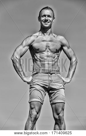 handsome man with sexy muscular body in shorts training sport has smiling happy face posing outdoor sunny summer on sky background black and white