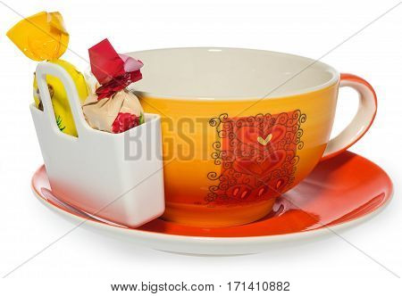 Empty coffee tea cup with storage on candy with two sweets . Cup and saucer decorated with hearts in color yellow orange red. Container for sweetmeats in white. Candy in yellow cream red. Dish on a white background with slight reflection.