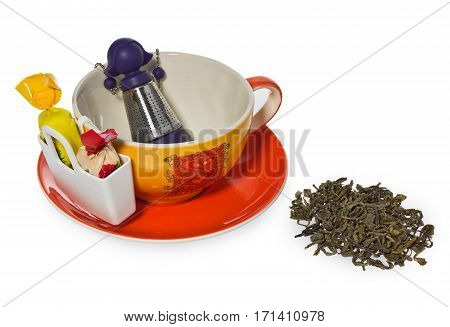 Coffee tea cup with purple silver infuser in the shape of a girl on a chain. Storage on candy and two sweets spilled tea. Cup and saucer decorated with hearts in color yellow orange red. Container for sweetmeats in white. Candy in yellow cream red.
