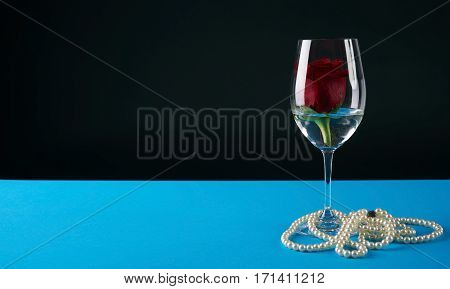 Wineglass with rosebud inside and pearl necklace on dark background. Love card concept with copy space. Valentine's day theme