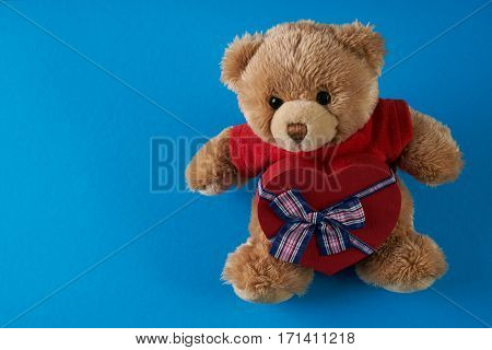 Teddy bear soft toy with heart shaped gift box on blue background Love card concept. Valentine's day theme