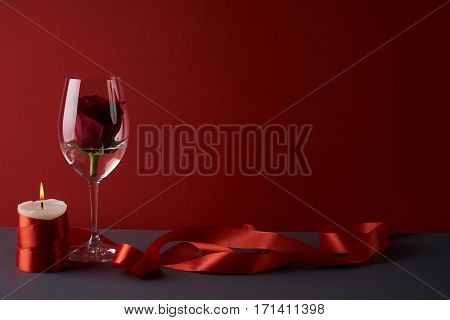 Wineglass with rosebud inside candle and red ribbon on red background. Love card concept with copy space. Valentine's day theme