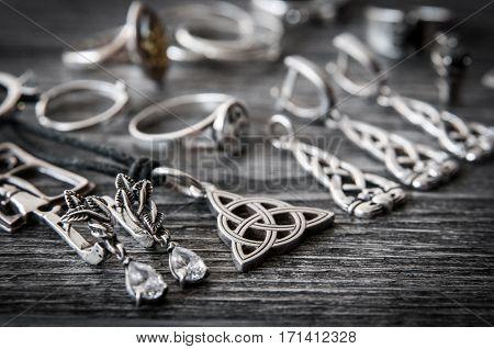 Beautiful ethnic Scandinavian Celtic Claddagh Silver jewelry Necklace, Earrings on a dark wood