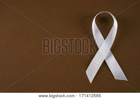 White awareness ribbon on brown background. Symbol of anti violence against women safe motherhood. Top vew with copy space