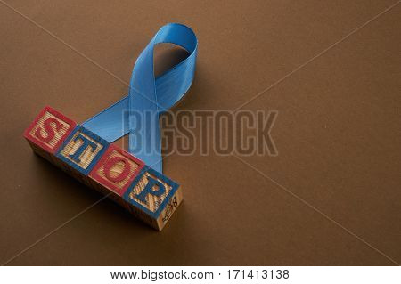 Prostate cancer awareness blue ribbon and cubes with letters. Stop word. Men healthcare concept