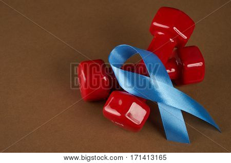 Prostate cancer awareness blue ribbon and dumbbells. Men healthcare concept