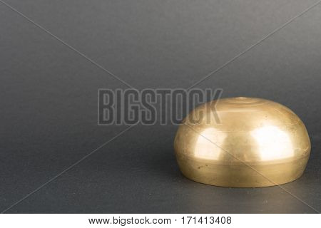 Golden Tibetian singing bowl on black background
