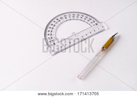 Pen and protractor on white background .
