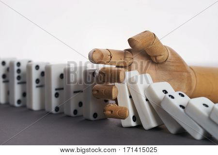 Wooden hand trying to stop toppling dominoes on table. Chain Reaction