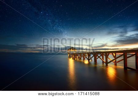 Beautiful night seascape with stars in the sky and pier stretching into the ocean. Summer Travel Vacation and Holiday concept - Wooden pier between sunset in North Sulawesi Indonesia.