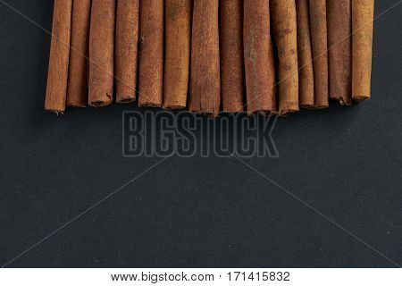 Cinnamon sticks on dark background top view. Copy space