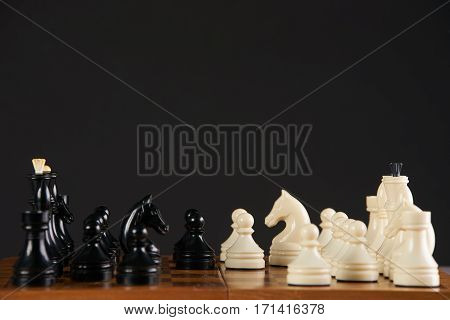 Chess pieces on chessboard on dark background