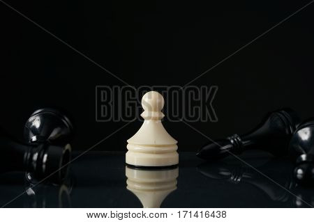 One white pawn staying and fallen black chess pieces . Last one standing business strategy concept on black background