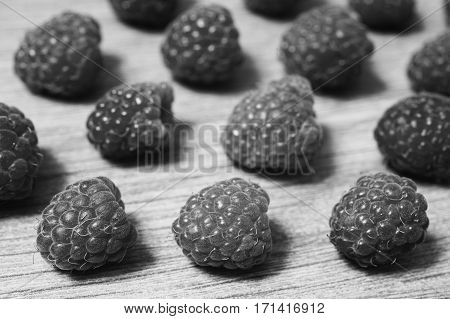 Black and white art photography monochrome ripe raspberry lie on a wooden background. Copyspace flat lay top view. Macro
