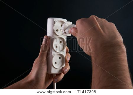 Hand putting plug in extension cord close up. Dark background