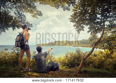 Couple tourists with backpacks enjoying view coast island Lombok on top of a mountain. Traveling along mountains and coast freedom and active lifestyle concept.