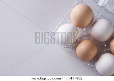Egg tray with white and brown eggs on white background. Close up with copy space