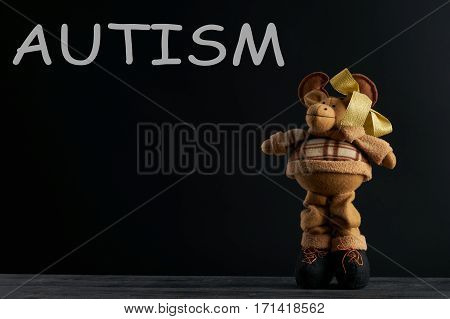Word AUTISM and Soft toy moose on dark background. Copy space