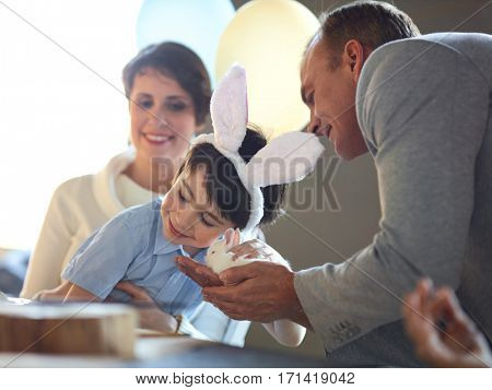 Parent giving fluffy pet to little boy