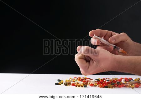 Male hands with medical syringe with drug and different colored medicine and types of pills . Doing inject in vein. On dark background.