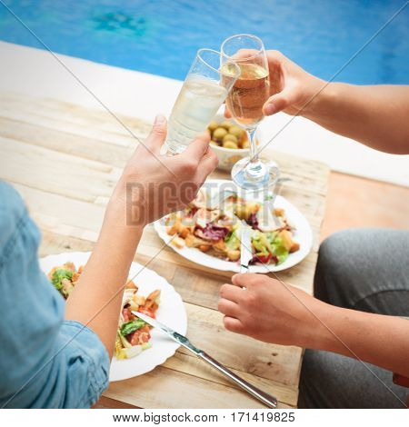 Closeup of hands with glasses toasting at table by swimming pool