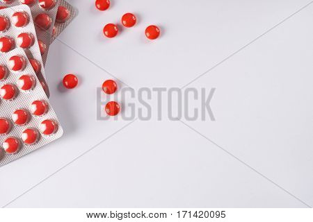 Red tablets in blister packs on white background Top view with copy space