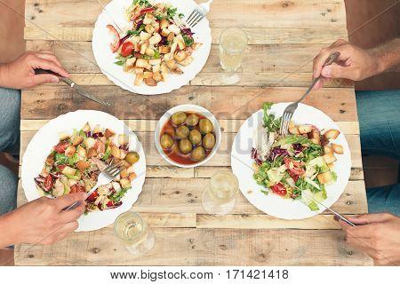 Three friends having informal dinner together. Salad, olives, champagne on vintage wooden table. Top view