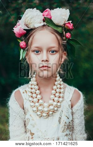 Summer portrait of a little girl with wreath of peony flowers. Fashion photo. Natural beauty. Russian girl. Authentic dramatic portrait.