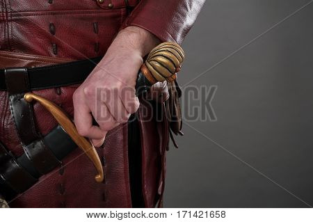 Medieval Knight Holding Hand On His Sword. Closeup