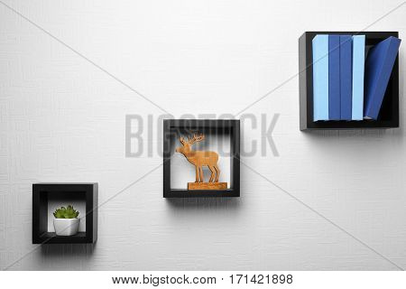 Set of books and decor on wooden shelves against light wall