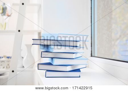Pile of books on windowsill