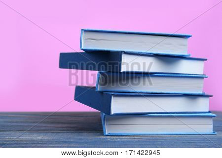 Books on wooden table and pink background
