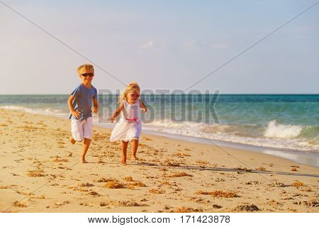 little boy and girl running at beach, family beach vacation