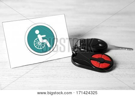 Car key and card with handicap sign on light wooden background