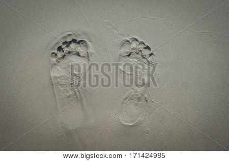 a pair of human footprints on the sand. Summertime period. Seaside photo. Background of footprints