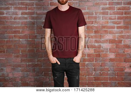 Closeup of man in claret red T-shirt on brick wall background