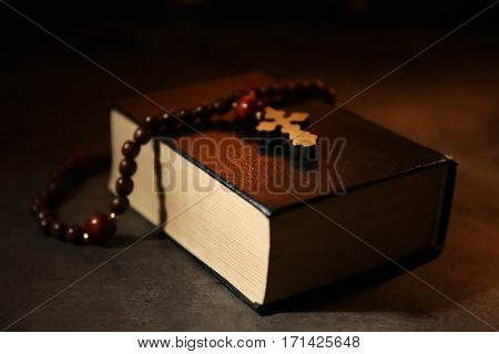 Bible with rosary on dark background