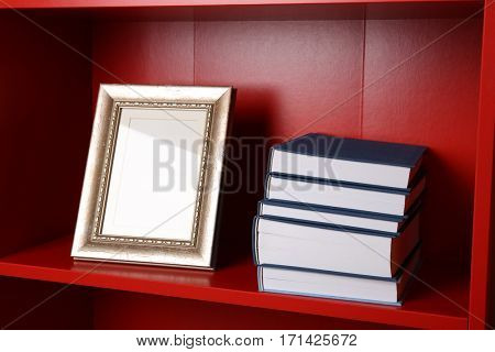 Stack of books on red wooden shelving