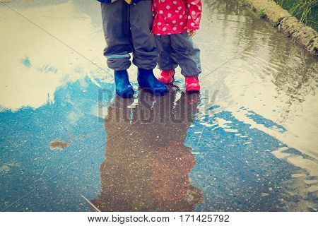 little boy and girl play in water puddle, kids seasonal activities