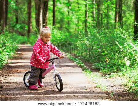 little girl riding bike in summer green forest