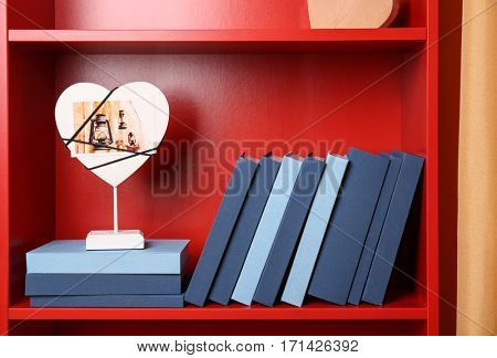 Different books with frame on red wooden shelving