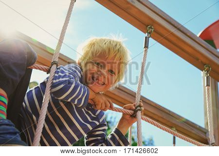little boy playing on monkey bars at playground, kids playtime