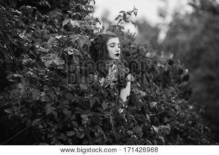 Black and white art photography monochrome girl in coat posing on a background of a bush with roses. Ring on a finger. Long hair. Pale skin. Pendant on the neck.