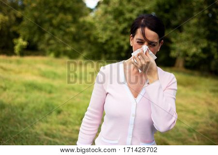 young woman suffering from a cold blowing her nose