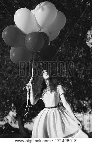 Black and white art photography monochrome girl with black and white balloons in nature against the sky. Happy woman. Fine art picture