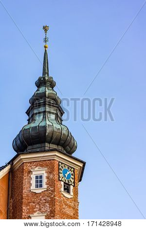 Clocktower of red bricks and a spire of copper against blue sky at Jagerspris castle Denmark - February 13 2017