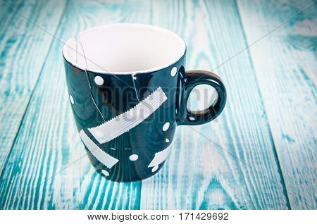 broken and glued with an adhesive plaster mug. The concept of the destruction of the relationship