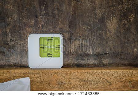 white alarm clock on headboard in the room