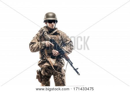 Armed male in military uniform holding machine gun and posing at camera.
