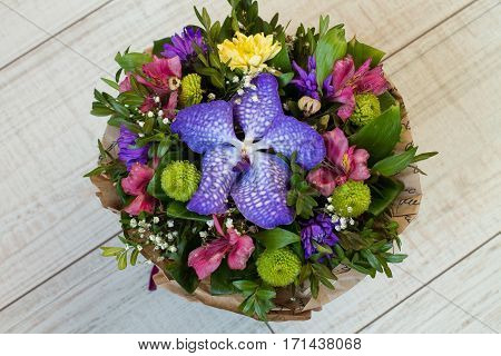 Bouquet of flowers (Purple orchid, alstroemeria, green chrysanthemum, gypsophila and buxus) in paper on wood. Aerial view.